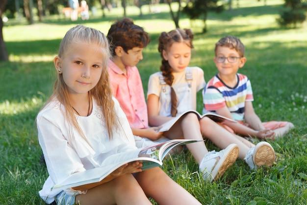 Hermosa niña leyendo un libro en el parque, sus amigos descansando sobre la hierba en el fondo