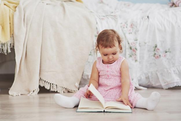Hermosa niña leyó el libro con su oso favorito sobre una suave manta de felpa
