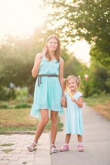 Hermosa niña con madre comiendo helado al aire libre en el parque