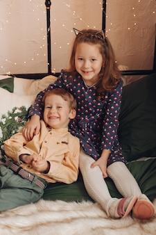 Hermosa niña manteniendo una sonrisa en su rostro mientras abraza a su hermano