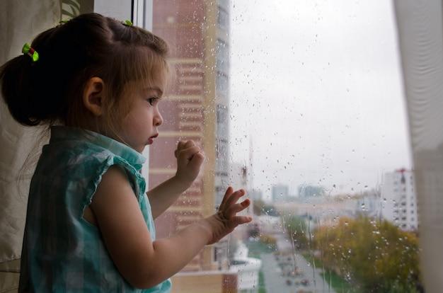 Hermosa niña mirando por la ventana bajo la lluvia