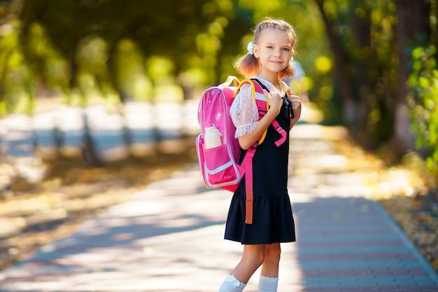 Hermosa niña con mochila caminando en el parque listo para volver a la escuela, caer al aire libre, concepto de educación.