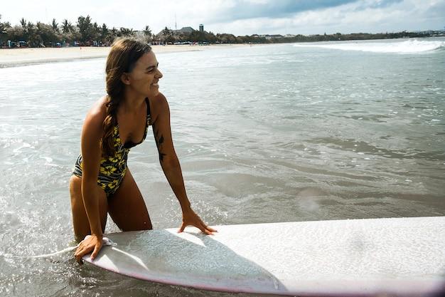 Hermosa niña montando en una tabla de surf en las olas