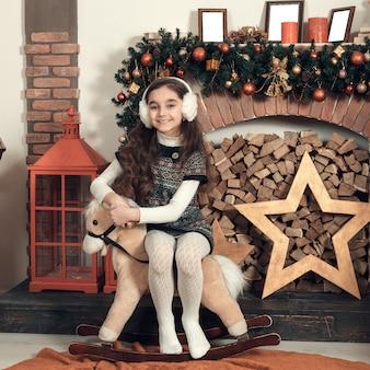 Hermosa niña morena con el pelo largo sentado en un caballo de juguete en navidad decorado habitación.