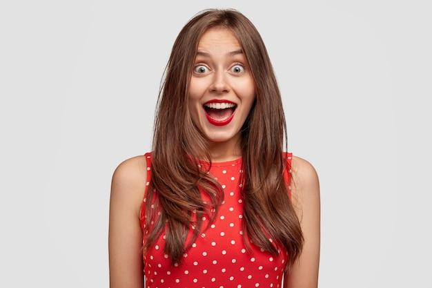 Hermosa niña no puede creer en su éxito, recibe una gran oportunidad, tiene expresión de sorpresa, abre la boca ampliamente