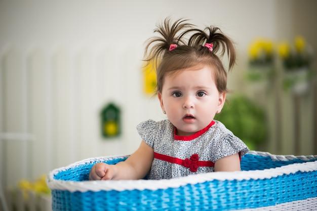 Hermosa niña de ojos marrones se sienta en la canasta