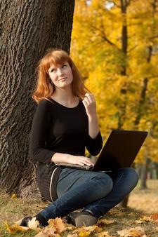 La hermosa niña en el parque otoño