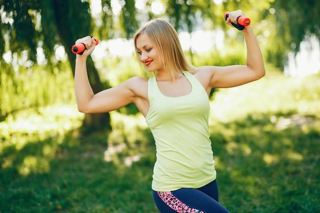 Una hermosa niña participa en el ejercicio de la mañana en el parque.