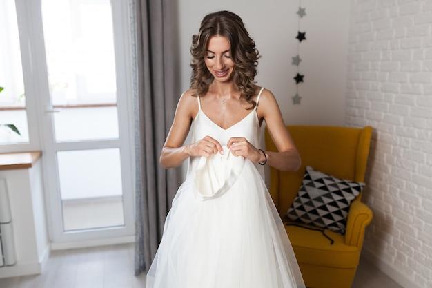 Una hermosa niña de pelo rizado, una futura novia que mide un vestido de novia en su casa antes de la boda.