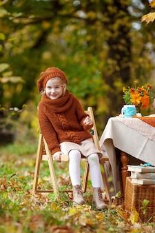 Hermosa niña en un picnic en el parque otoño