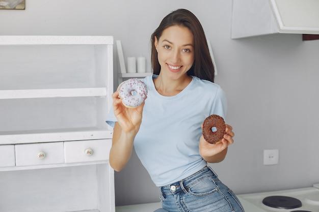 Hermosa niña de pie en una cocina con donut