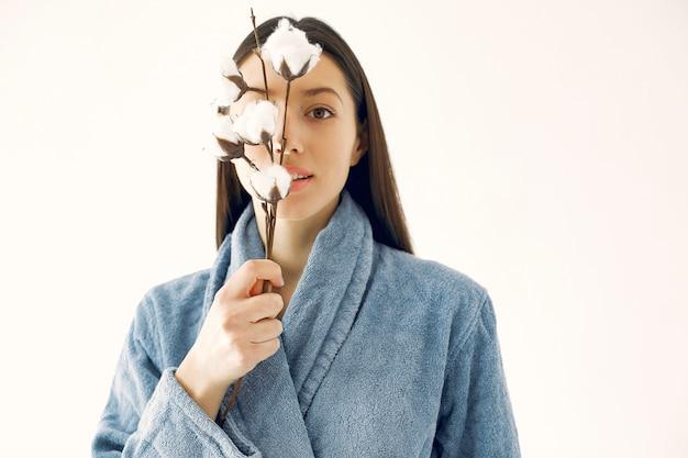 Hermosa niña de pie en un estudio con flores de algodón