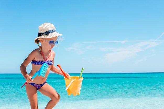 Hermosa niña en la playa divirtiéndose con herramientas de arena