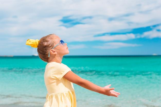 Hermosa niña en la playa divirtiéndose