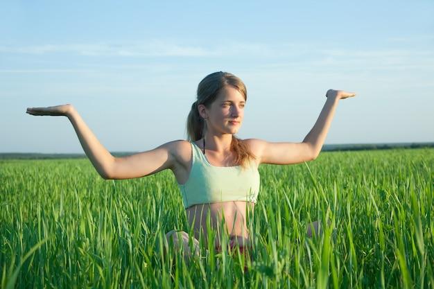 Hermosa niña practicando yoga contra el cielo azul