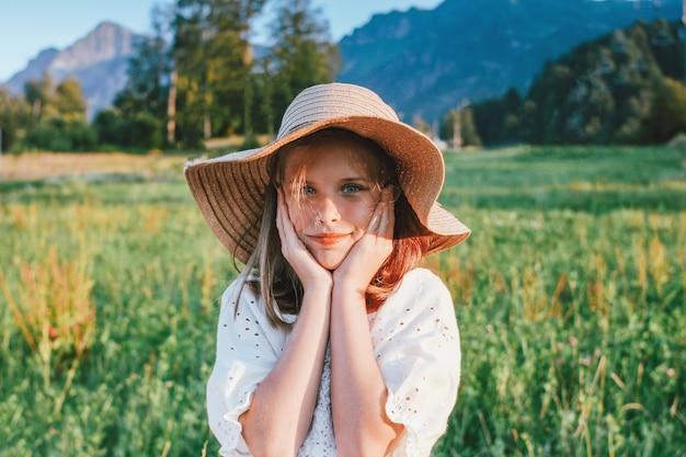 Hermosa niña preadolescente romántica en sombrero de paja contra el fondo de las montañas, hora dorada