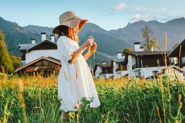 Hermosa niña preadolescente romántica en sombrero de paja recogiendo flores contra el fondo de hermosas casas en la montaña, escena rural al atardecer