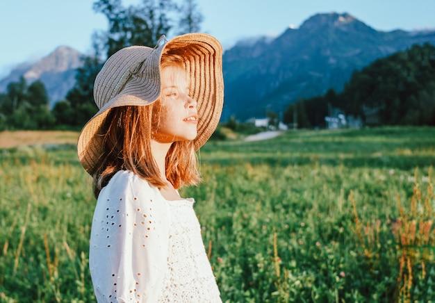 Hermosa niña preadolescente romántica con sombrero de paja sobre fondo de hermosas casas en la montaña, escena rural al atardecer