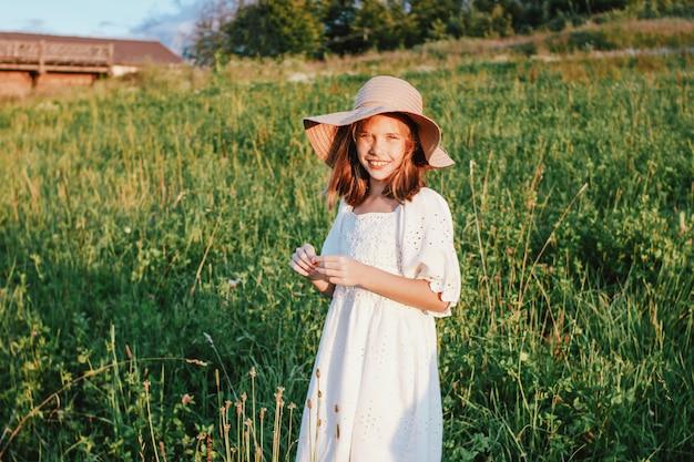Hermosa niña preadolescente romántica con vestido blanco y sombrero de paja en el prado verde, hora dorada