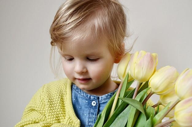 Hermosa niña con un ramo de tulipanes amarillos