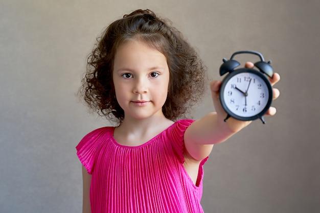 Hermosa niña rizada con un reloj de escritorio