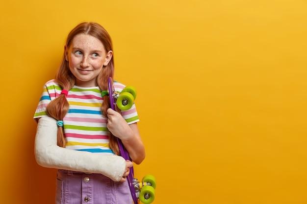 Hermosa niña se rompió el brazo después de caerse de la patineta, disfruta de los deportes extremos, usa yeso, se lesiona después de un accidente durante el verano, espera una recuperación rápida y volver a montar, aislado en amarillo