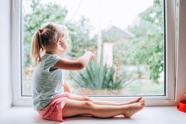 Una hermosa niña rubia con cuento de caballo mirando por la ventana en un día de verano húmedo, frío y lluvioso y mostrando en algún lugar con el dedo
