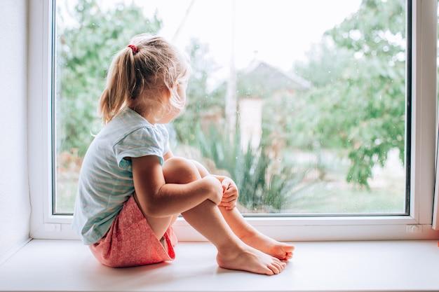 Una hermosa niña rubia mirando por la ventana en un día lluvioso frío y húmedo