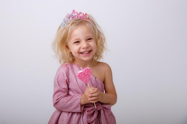 Hermosa niña rubia con una piruleta en forma de corazón
