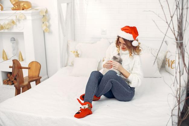 Hermosa niña sentada en una cama con lindo gatito