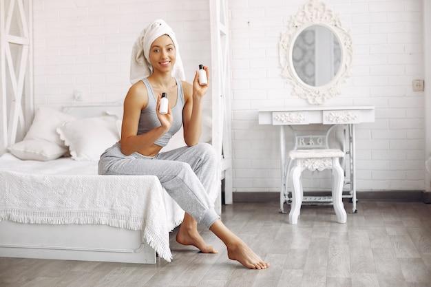 Hermosa niña sentada en una cama con productos de belleza