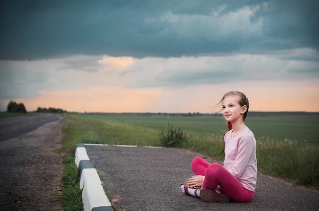 Hermosa niña sentada en el camino