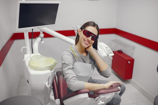 Hermosa niña sentada en el consultorio del dentista