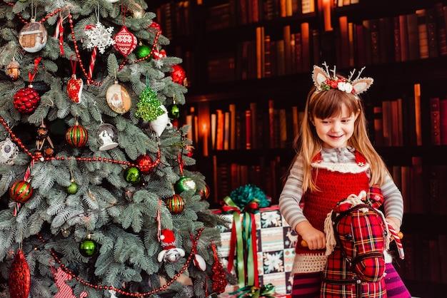 La hermosa niña sentada en el hobbyhorse cerca del árbol de navidad
