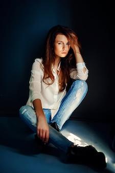 Hermosa niña sentada en el piso en la oscuridad