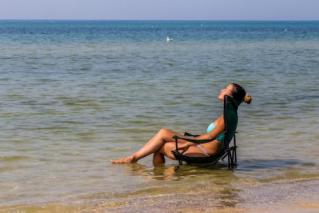 Hermosa niña sentada sola en el mar, bonito bronceado