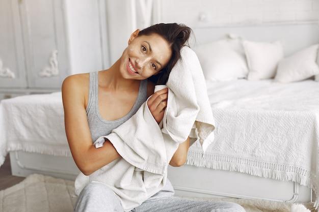 Hermosa niña sentada en su casa cerca de la cama