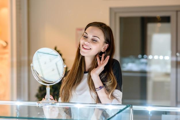 Hermosa niña sonriendo y haciendo compras en el centro comercial.