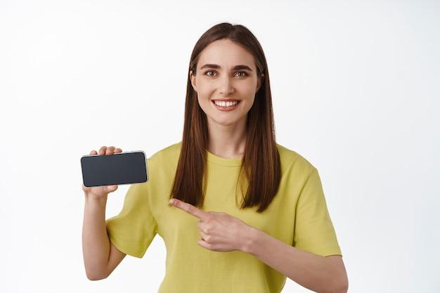 Hermosa niña sonriente apuntando a la pantalla horizontal del teléfono inteligente, mostrando el anuncio en el teléfono, interfaz de la aplicación, de pie en una camiseta en blanco