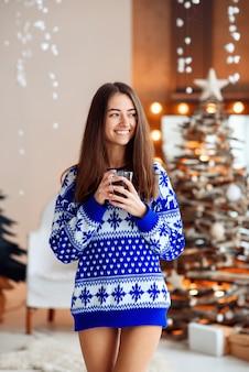 Hermosa niña sonriente en un cálido suéter de vacaciones con una taza de té caliente