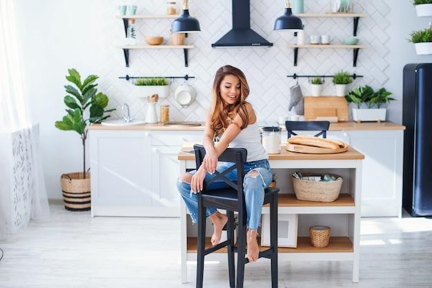 Hermosa niña sonriente en camiseta blanca se sienta en la elegante cocina blanca en la mañana.