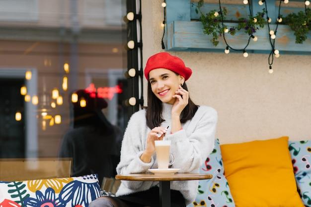 Hermosa niña sonriente feliz en una boina roja está sentado en una mesa de un café de la calle y bebiendo café con leche