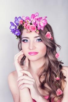 Hermosa niña sonriente con flores en el pelo