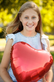 Hermosa niña sonriente con globo corazón