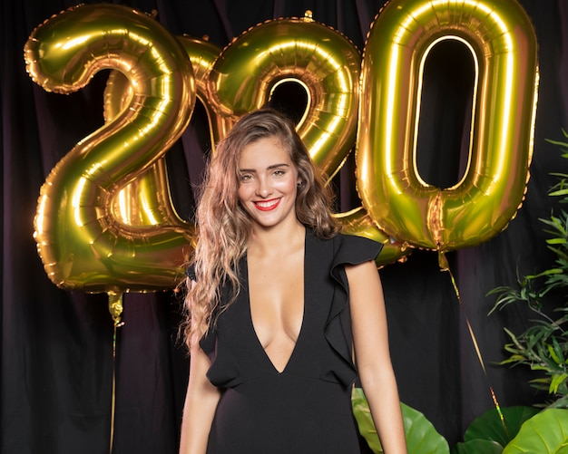 Hermosa niña sonriente con globos de año nuevo 2020