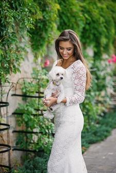 Hermosa niña sonriente hermosa en elegante vestido blanco de encaje con un perrito blanco en las manos
