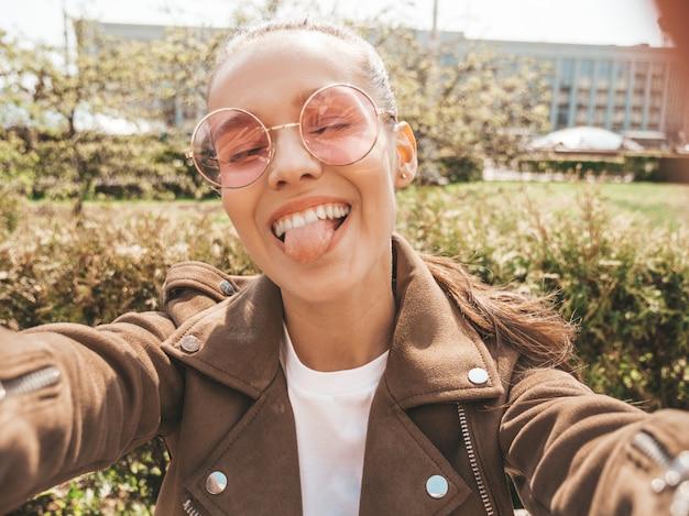 Hermosa niña sonriente en jeans y chaqueta hipster de verano modelo tomando selfie en teléfono inteligente y mostrando la lengua