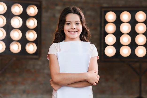 Hermosa niña sonriente de pie delante de la luz de la etapa