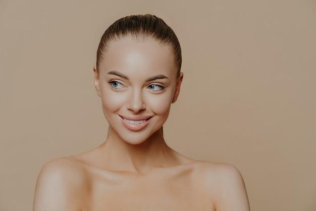 Hermosa niña sonriente con piel limpia, maquillaje natural y dientes blancos sobre beige