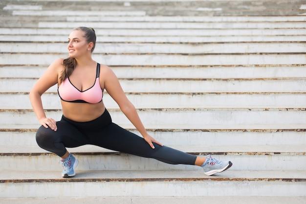 Hermosa niña sonriente plus size en top deportivo y polainas haciendo deporte en las escaleras mirando con alegría a un lado mientras pasa tiempo al aire libre